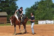 une personne sur un cheval avec une personne à coté