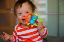 bébé avec une trisomie qui tient un jouet