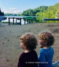 2 enfants de dos qui regardent un lac